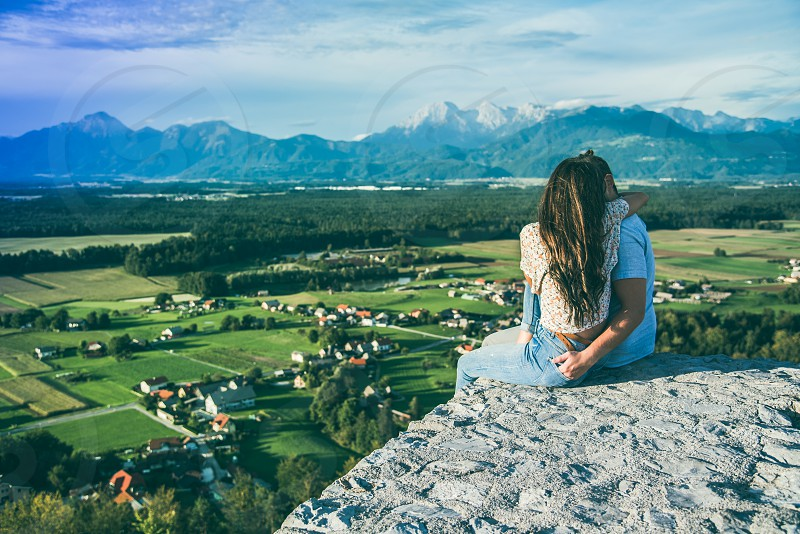 Couple in love seating on the edge of stone wall looking down on landscape. photo