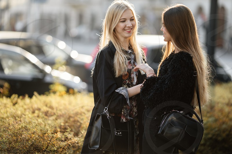 Two pretty girls sit on the bench street talk and smile to each other photo
