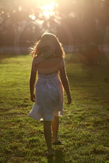 woman wearing white dress standing on green grass photo