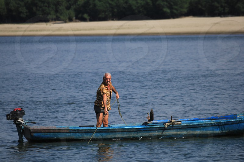 man in blue bass boat holding brown and grey fishing rod bear seashore during day time photo