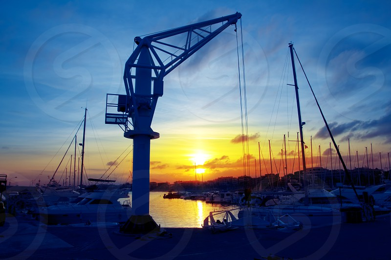 boats crane at sunset in marina port of Salou Tarragona Spain photo