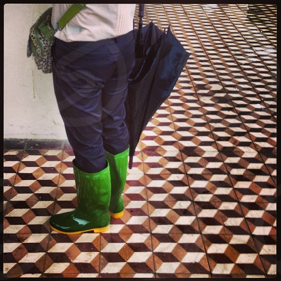 person standing wearing green and yellow rain boots photo
