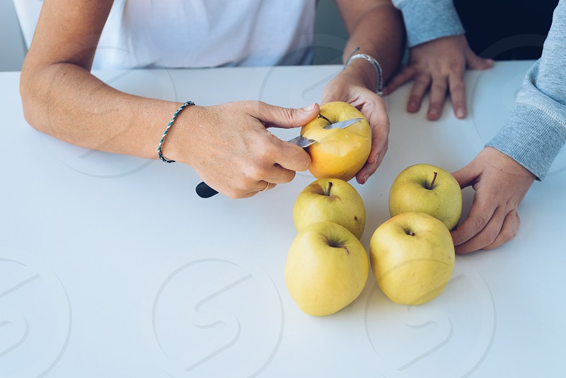 Close up of mother peeling green apples on table while her daughter is taking one photo