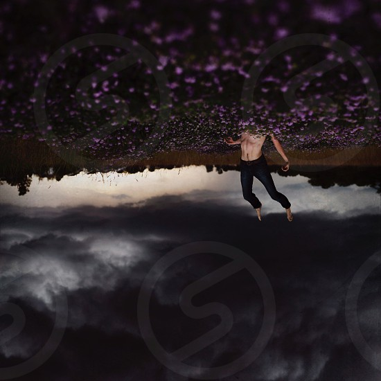 topless man wearing black pants diving in purple flower field under dark cumulonimbus clouds photo