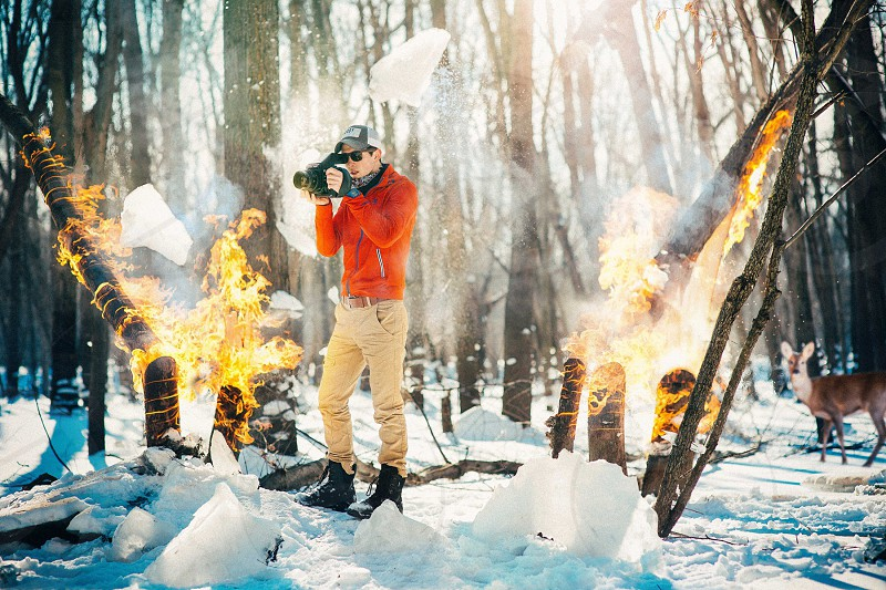 Adventure photographer.  A composite of an adventure photographer in a winter woods with snow on the ground and fire on the trees around him.  photo