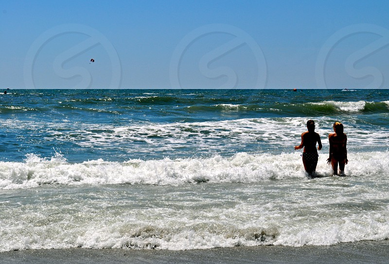 Cold ocean water splashes over two women photo