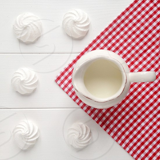 baked meringues by a white ceramic pitcher photo
