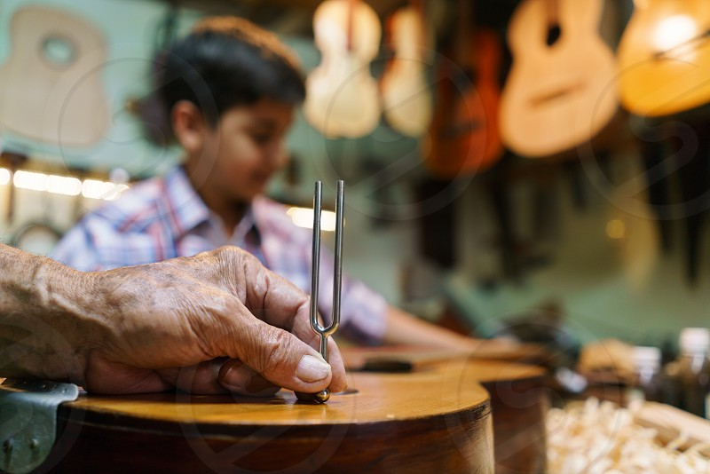 child kid boy man guitar string hand holding diapason playing classic A acoustic caucasian classical crafts craftsman family fixing grandchild grandfather grandpa grandson hispanic hobby job learning lute luter maker music musical note persons palette people precision preteen profession shop string instrument studio teaching team teamwork tune work workshop photo