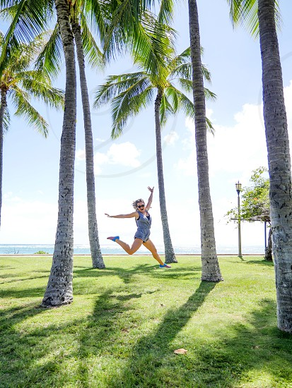 Fitness woman jump work out with joy on the beach park grass at Hawaii  photo