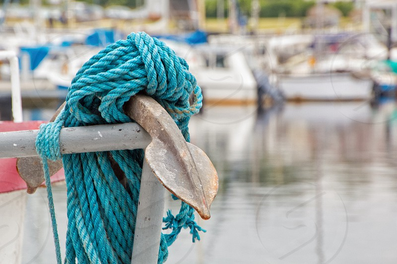Turquoise nautical rope wrapped around an anchor hanging on the bow of a sailboat. photo