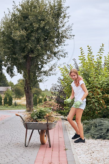 Teenage girl working at a home garden. Candid people real moments authentic situations photo