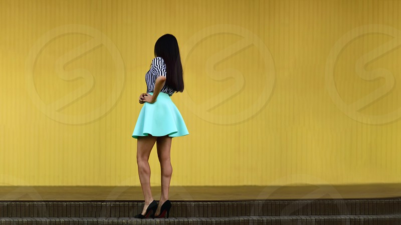 woman in black and white stripe shirt and teal skirt facing on yellow wall photo