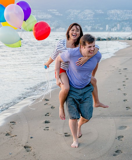 couples with balloons at the beach laughing photo