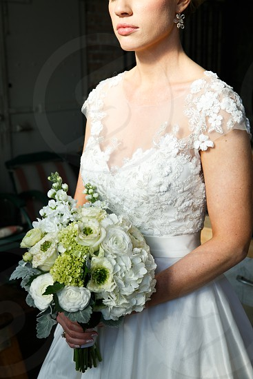 bride holding white and green flower bouquet photo