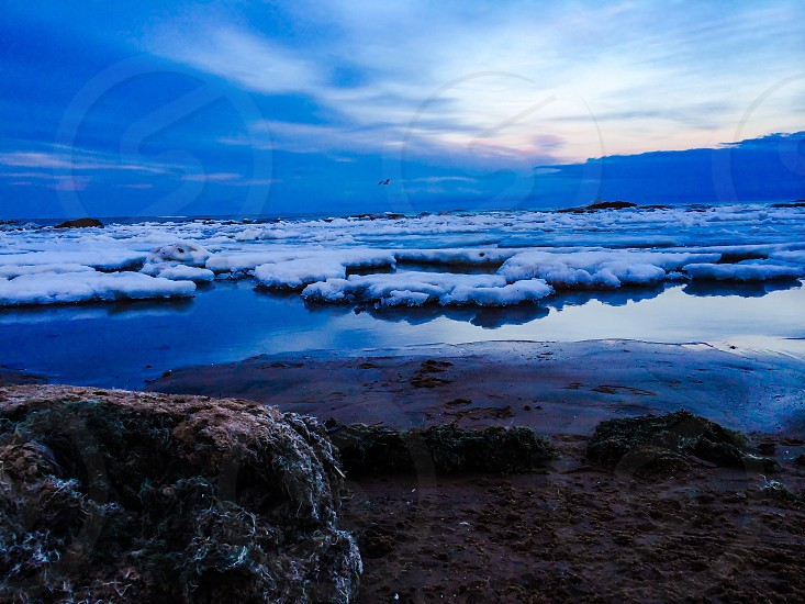 Beach winter lake dusk ice blue water clouds photo