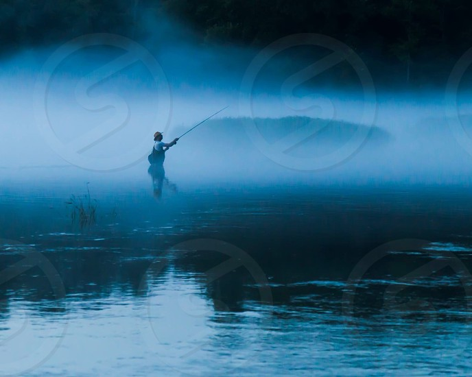man in tan hat white t shirt and black overall waders fishing in glassy lake in white fog in early morning under dark sky with trees in distance photo