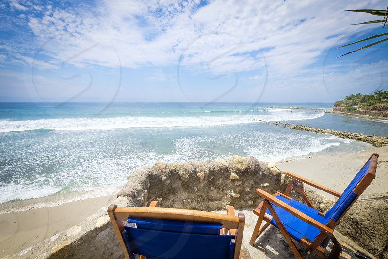 Two beach chairs at elevated terrace over looking a beautiful beach at the Pacific coast at Riviera Nayarit Mexico. photo
