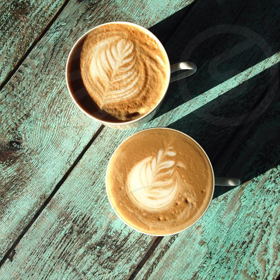 leaf cappuccino on white ceramic mug photo