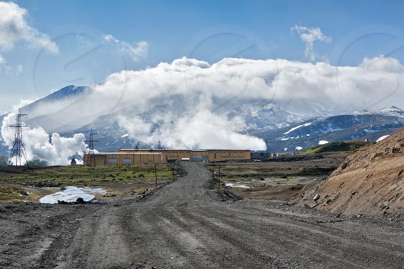 MUTNOVSKY VOLCANO KAMCHATKA RUSSIA - SEP 21 2011: View of the road to Mutnovskaya Geothermal Power Station on background active Mutnovsky Volcano. Eurasia Russia Far East Kamchatsky Krai. photo