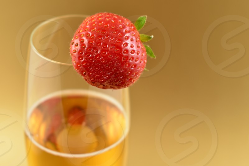 Strawberry with champagne. Glass of champagne with strawberry stock images. Champagne on a golden background with copy space for text. Festive golden background. Valentines Day concept photo