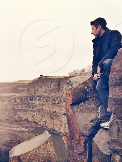 man standing on a cliff  photo
