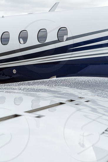 Business jet's wing and windows in the rain photo