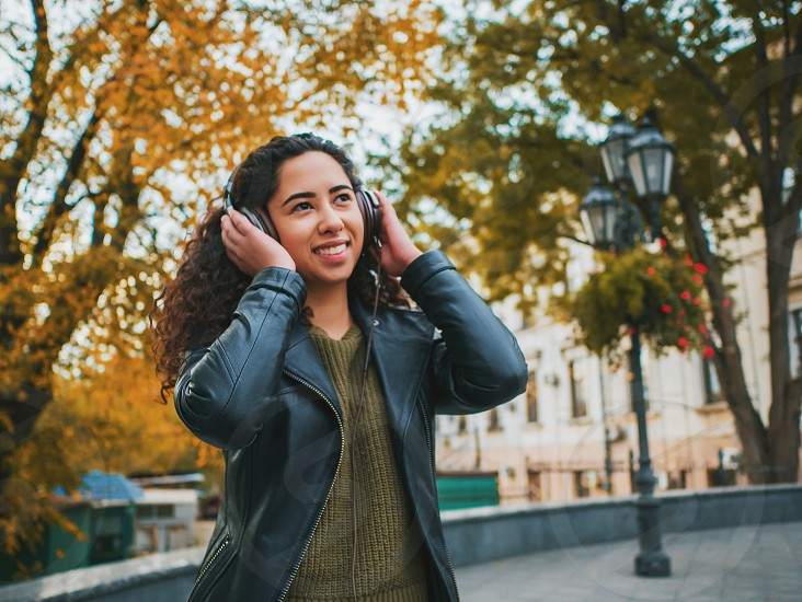 Latin curly haired girl listening music in headphones in autumn park. Beautiful young hispanic lady smiling singing and enjoying melody outdoor. photo