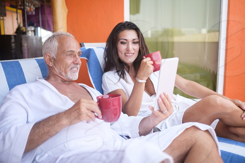 Older man and young woman using a tablet computer while enjoying coffee in bathrobes on loung chairs Nuevo Vallarta Nayarit Mexico photo