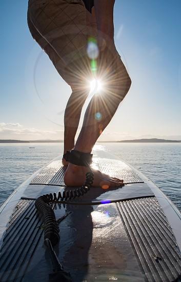 Surfing surfer sun crown beams legs wet  photo