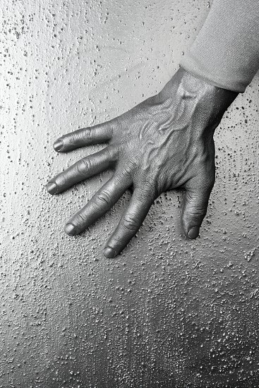 male futuristic man silver hand over textured steel background photo