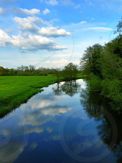 blue and white cloudy sky over grass field and river photo