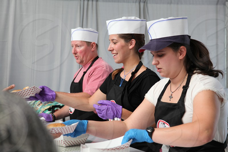 three person wearing sailor's hat while serving some food packages photo