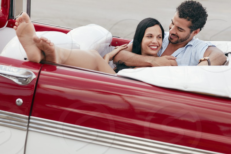 couple; hug; hugging; lying; car; auto; woman; 20s; 30s; adults; affection; automobile; barefoot; bonding; boyfriend; cabriolet; cheerful; convertible; crossed; dating; feet; female; flirting; fun; girlfriend; happy; hispanic; husband; joy; latina; love; lovers; male; man; passion; people; persons; red; romance; seat; smiling; street; together; travel; two; urban; vehicle; vintage; wife; young photo