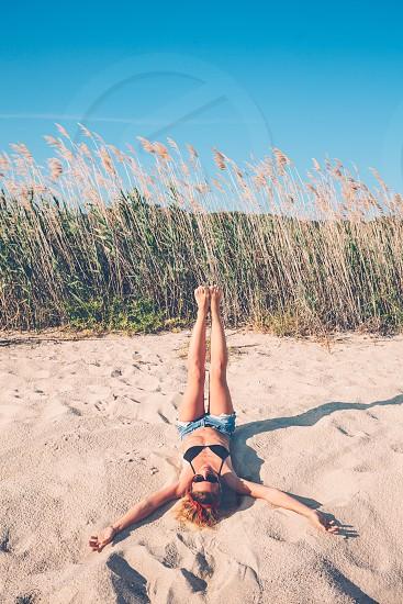 Young woman lying on the beach enjoying herself photo