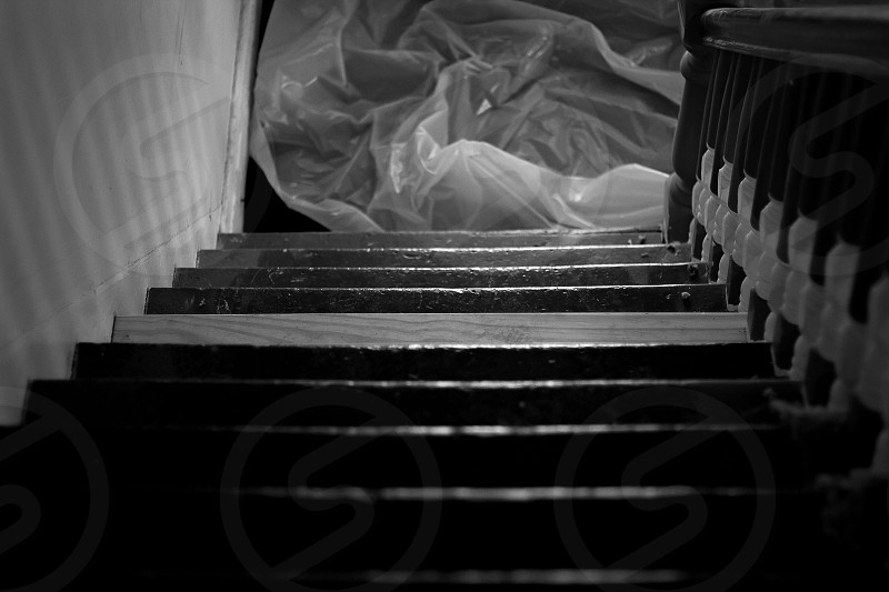 textile under wooden stairs in grayscale photography photo