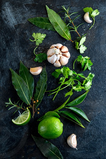 Fresh herbs and spices on black background. - garlic laurel lime rosemary parsley pepper. photo