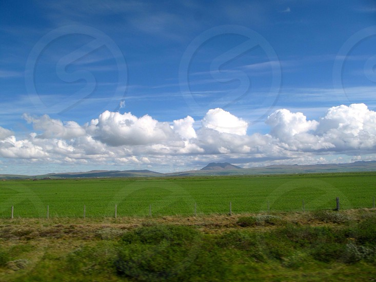 green field and white clouds view photo