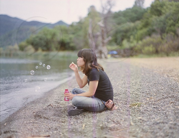 woman sitting near the river blowing bubbles photo