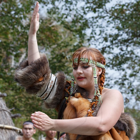 KAMCHATKA REGION RUSSIA - SEP 14 2013: Concert on Itelmen national holiday of thanksgiving nature Alhalalalay. Expression young woman (ensemble Northern Dawns) dancing in clothing aborigine of Kamchatka Peninsula. photo