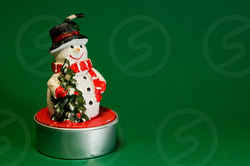Snowman figurine isolated on green background Christmas decoration concept interior design photo