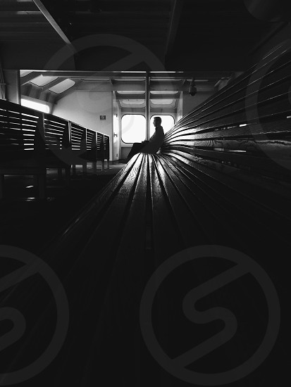 man sitting on waiting bench on grayscale photography photo