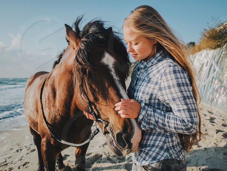 Beautiful fair-haired girl in armor with a horse on the background of the sea. photo