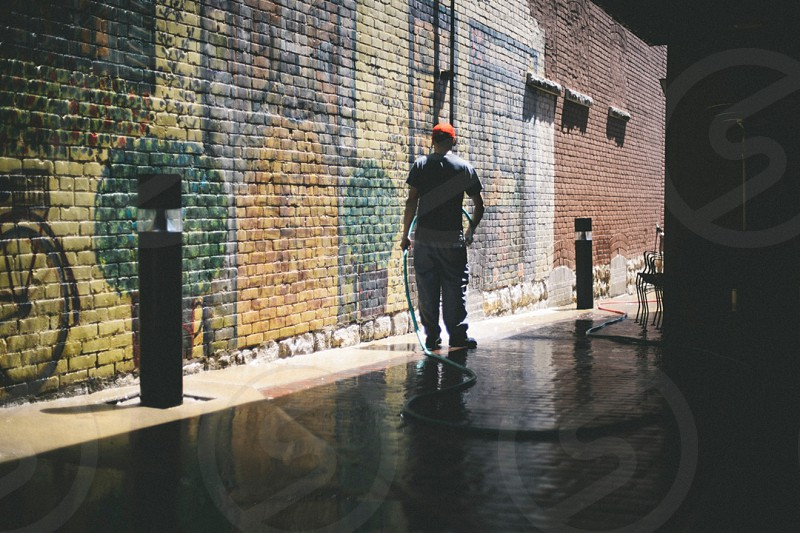 alleyway with person using hose photo
