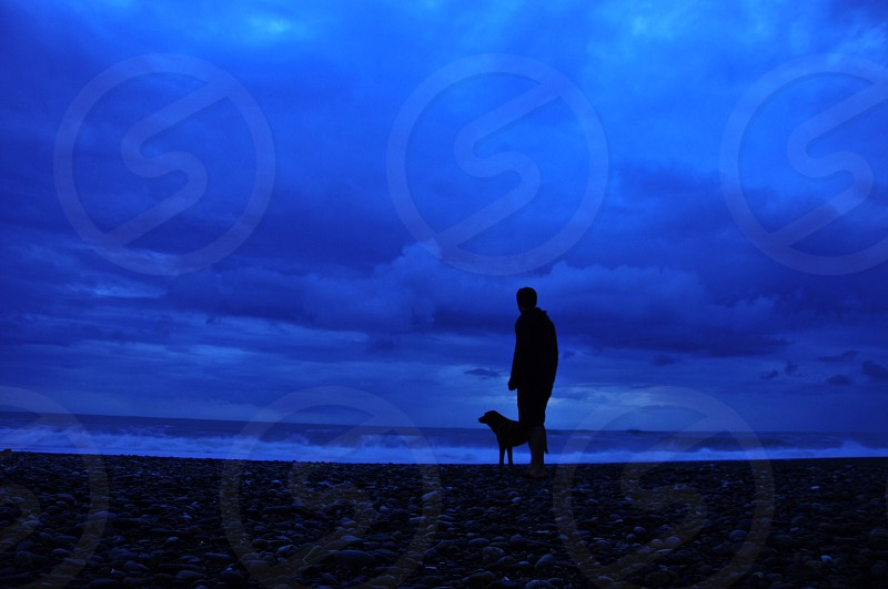 man standing by the seashore with dog photo