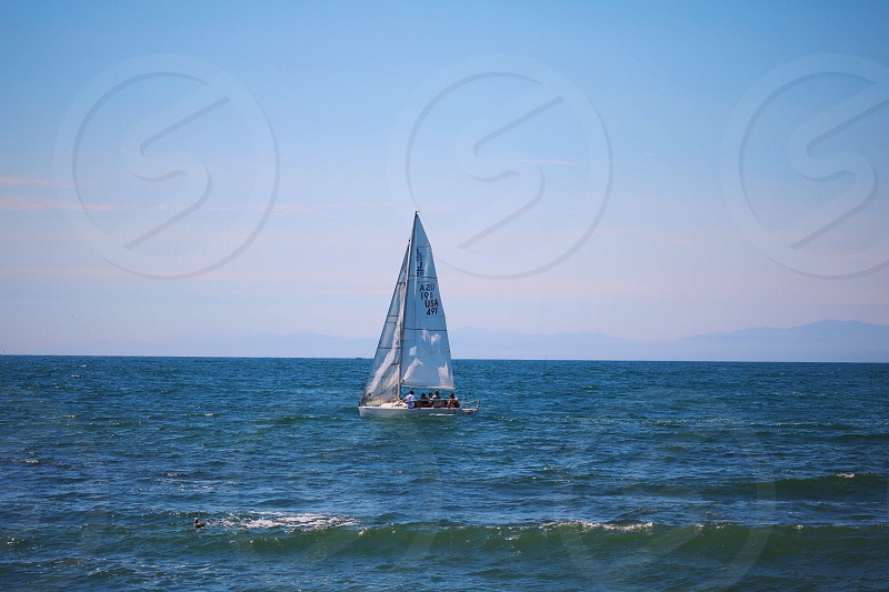 photo of blue and white sailing boat on body of water photo