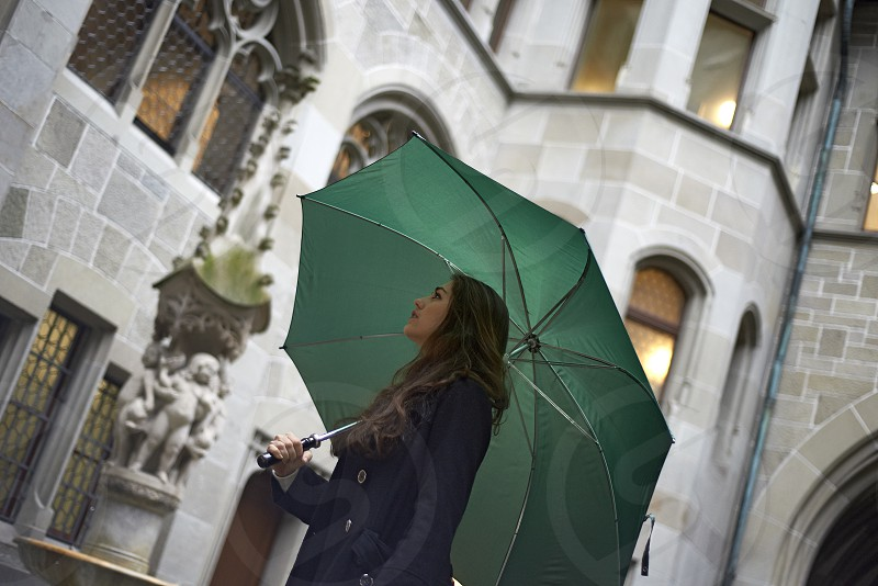 Affluent young business woman holding a large green umbrella and looking around taing in the sights of Zurich city centre photo