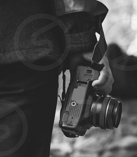 person holding camera in right hand black and white photo photo
