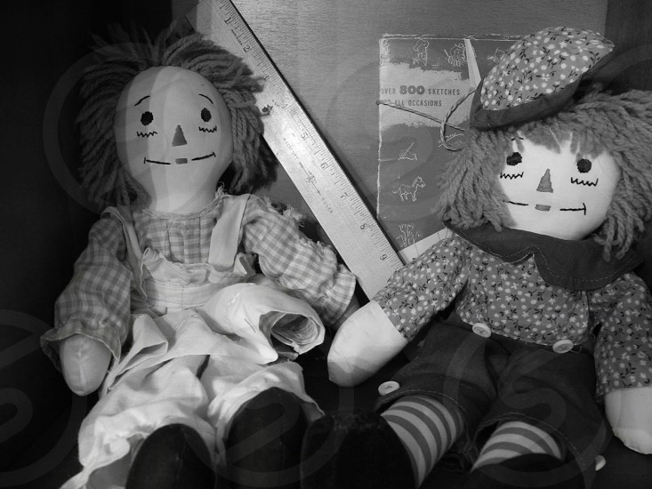 raggedy anne and andy dolls sitting on shelf photo