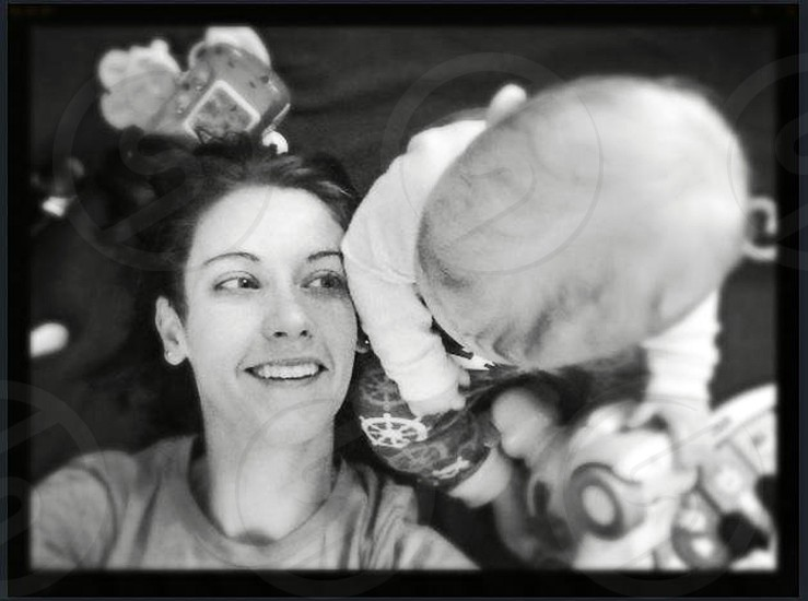 baby sitting beside lying woman gray scale photography photo