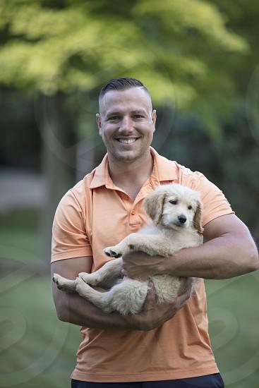 Man cuddle puppy photo